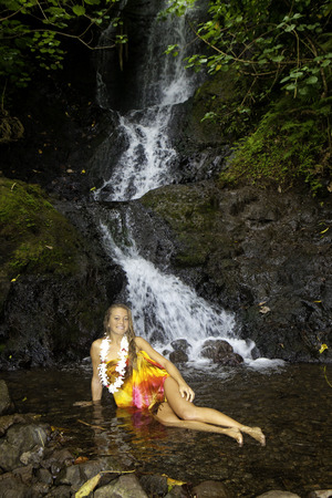 pareo: young woman in a tropical waterfall in Hawaii