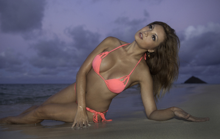 girl in pink bikini at the beach at sunset photo