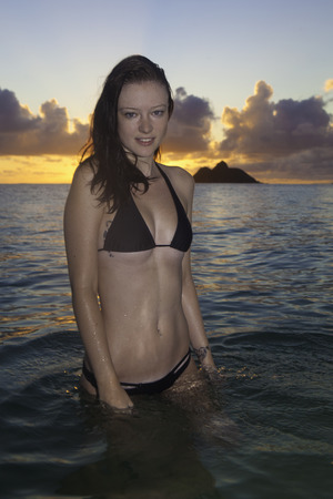 girl in bikini on the beach at sunrise in hawaii photo