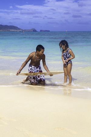 skim: boy teaching sister to skim board Stock Photo