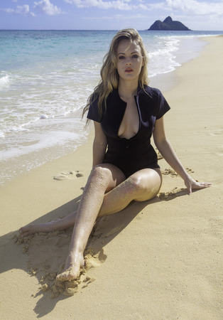 beautiful blond girl in wetsuit at the beach Stock Photo