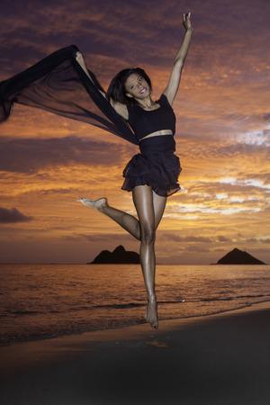 beautiful black girl dancing on the beach at sunrise photo