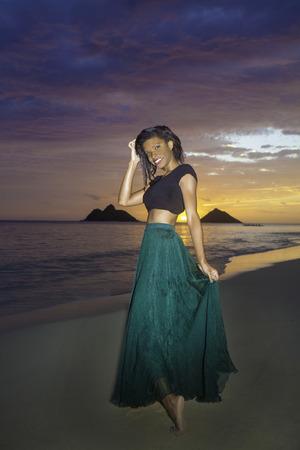 black girl in dress on the beach at sunrise in hawaii photo