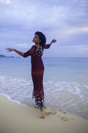 happy black girl on the beach in a dress photo