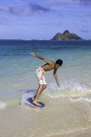 skim: polynesian boy riding his skim board in Hawaii Stock Photo