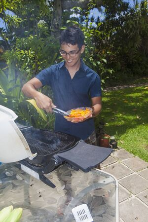 barbecuing: asian man barbecuing in his garden