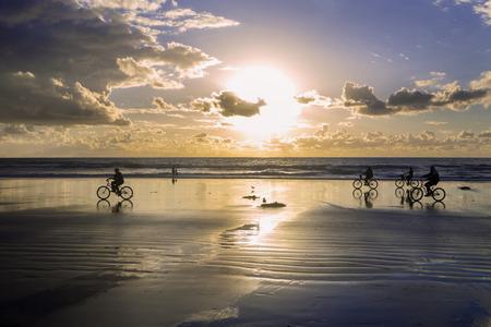 beach sunset: bikes on the beach at sunset