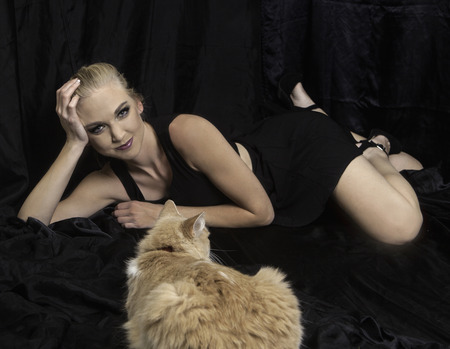 blond woman on black satin with her cat