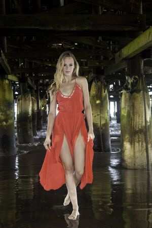 beautiful woman in red dress under pacific beach pier