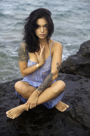 woman on lava rocks by the ocean