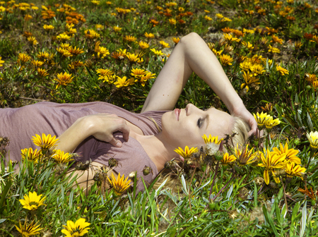 lonely person: blond girl in field of flowers