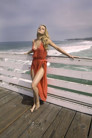 beautiful woman in red dress on a pier Stock Photo
