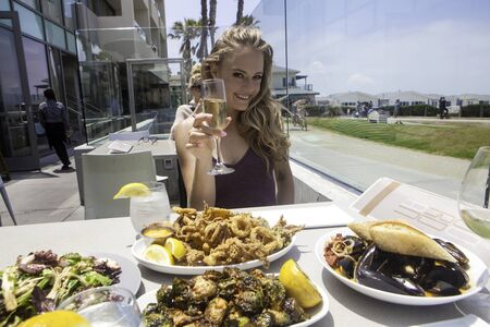 beautiful blond at beach side lunch with champagne Stock Photo