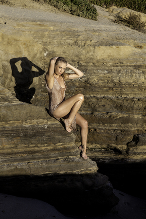 beautiful blond in a gown on a rocky cliff Stock Photo