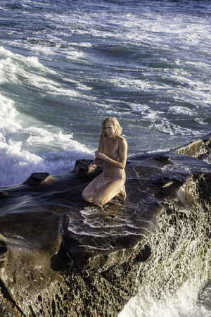 beautiful blond in a gown on rocks by the ocean