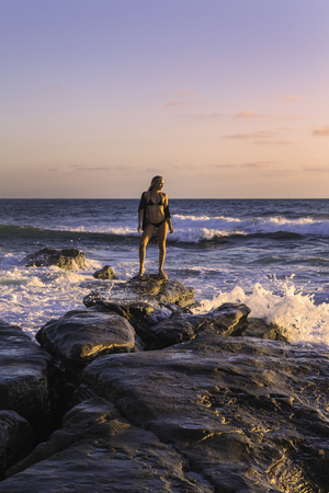 beautiful blond on rocks by the ocean Stock Photo