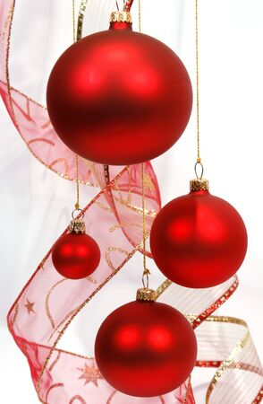 Hanging red glass balls with the ribbon on the white background