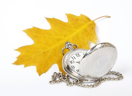 Yellow oak leaf and pocket watch on the white background photo