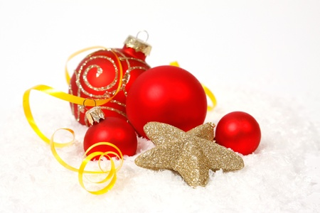 christmas bulbs: Red  baubles and golden star on the snow Stock Photo