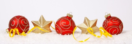 Red-golden baubles and golden stars on the snow