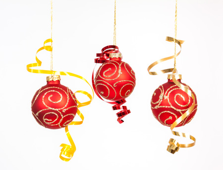 Red baubles with the ribbon on the white background