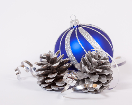 Bauble and cones with the ribbon on the white background