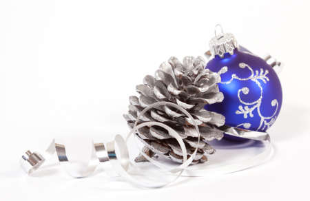 Bauble and cone with the ribbon on the white background