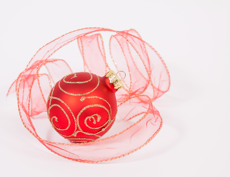Red-gold bauble with the ribbon on the white background