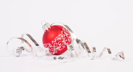 Red bauble with the ribbon on the white background