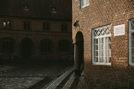 Corner of an old brick house with an underpass supporting a stone column enlightened in the afternoon sun, with a wet granite road around the old Denmark village of Ribe