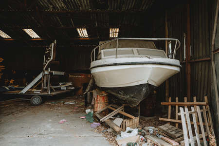 Forgotten abandoned old boat covered with layer of dust hidden in old barn full of mess and other old things 免版税图像