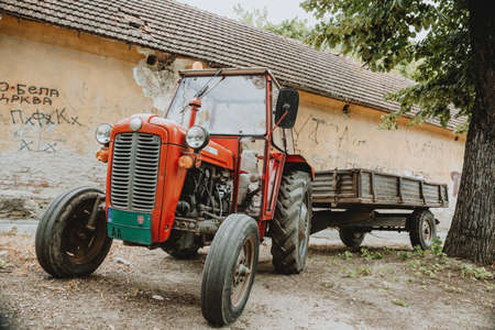One old red tractor with trailer standing alone in front of building on the gravel street in shadow under the tree during the summer sunny day in Serbia