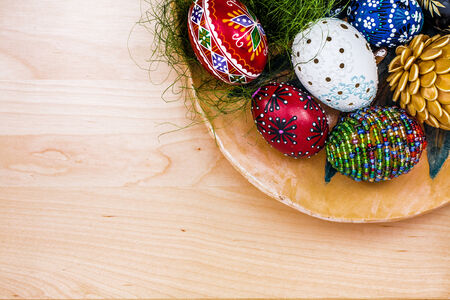 Top view of easter eggs in wooden bowl on wooden backgroud.