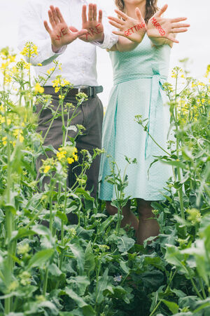 Couple before wedding with red sign on their hands, we are getting married, colza field, romantic photo, engagement photo, gilr with turquoise dress, vintage color