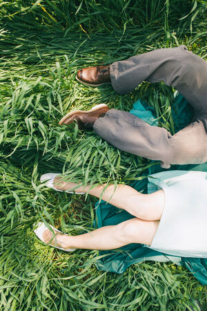 Laying couple in the high grass, top perspective, only legs, engagement photo, before wedding, picnic, sunny day, romantic photo, without face, gilr with turquoise dress, vintage color Stock Photo
