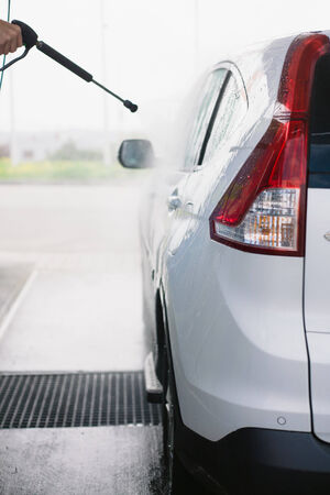 shiny car: Spray gun, held by hand, used to wash a white off-road car, splashing water, shiny landscape background, vertical, half of car, on gas station