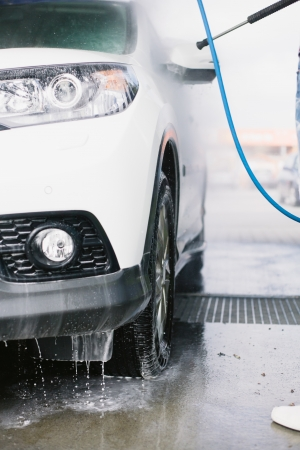 Spray gun, held by man, used to wash a white off-road car, splashing water, parking lot background, vertical, detail of car, on gas station, low perspective, impressive atmosphere