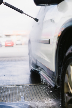 Spray gun, held by man, used to wash a white off-road car, splashing water, parking lot background, vertical, detail of car, on gas station, low perspective photo