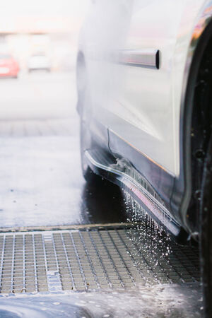 Spray gun, used to wash a white off-road car, splashing water, parking lot background, vertical, detail of car, on gas station, low perspective, freezed water