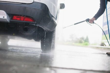 Spray gun, held by man, used to wash a white off-road car, splashing water, shiny landscape background, horizontal, detail of car, on gas station, low perspective, impressive atmosphere