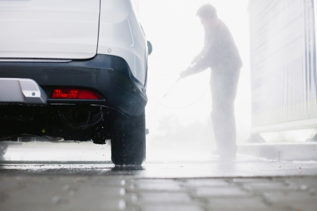 Spray gun, held by man, used to wash a white off-road car, splashing water, shiny background, horizontal, half of car, on gas station, low perspective, impressive atmosphere Stock Photo