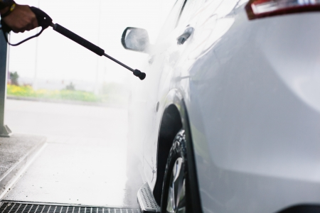 shiny car: Spray gun, held by hand, used to wash a white off-road car, splashing water, shiny landscape background, horizontal, detail of car, on gas station, Stock Photo
