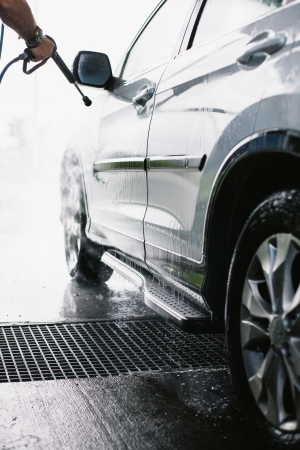 Spray gun, held by hand, used to wash a white off-road car, splashing water, shiny background, vertical, half of car with reflection, on gas station
