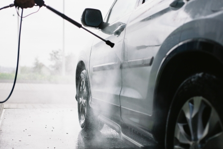 washing hand: Spray gun, held by hand, used to wash a white off-road car, splashing water, shiny landscape background, horizontal, half of car, on gas station, low perspective Stock Photo