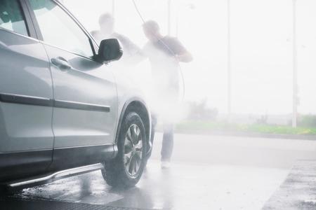 lavandose las manos: Pistola de pulverizaci�n, que se celebr� por el hombre, que se utiliza para lavar un coche todoterreno blanco, salpicaduras de agua, el paisaje de fondo brillante, horizontal, medio de auto, en la estaci�n de gas, la perspectiva de baja, impresionante ambiente Foto de archivo