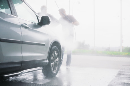 dirty car: Spray gun, held by man, used to wash a white off-road car, splashing water, shiny landscape background, horizontal, half of car, on gas station, low perspective, impressive atmosphere