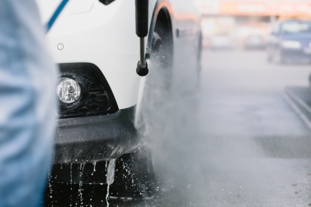 Spray gun, held by man, used to wash a white off-road car, splashing water, parking lot background, horizontal, detail of car, on gas station, low perspective, impressive atmosphere