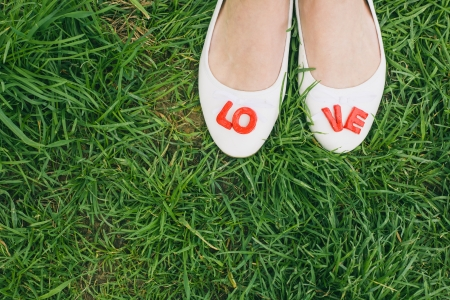 red shoes: White woman shoes with red LOVE letters, green grass background, top perspective, before wedding, engagement photo, vintage color
