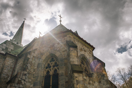 Catholic church in the forest in Czech Republic, cloudy sky with sun
