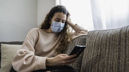 Coronavirus. Teenager talking to her friends on the phone, protected against the virus. Pandemic. Social distance